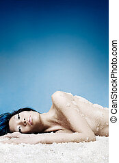 Ice queen - Asian girl laying on crushed ice, artistic...