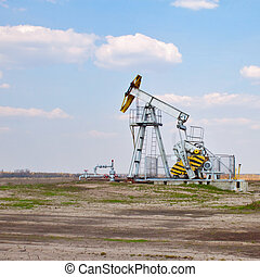 oil derrick - An oil well with the pump jack in action