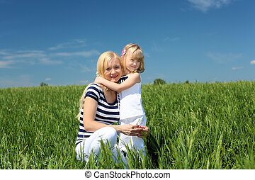 mother with her daughter outdoors in summer day