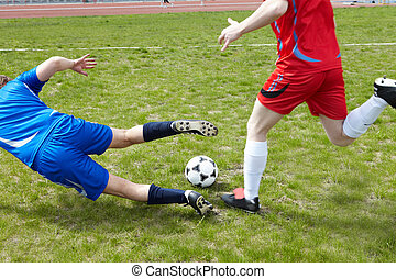 During game - Two footballers chasing ball on grass-field...