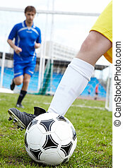 Playing soccer - Photo of soccer ball being kicked by...