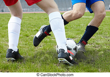 Kicking ball - Image of footballers legs kicking soccer ball...