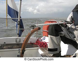 Man navigating his sailboat