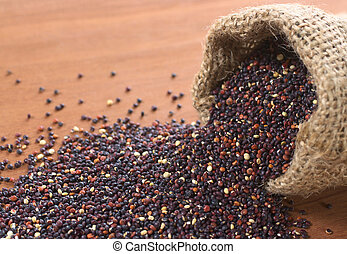 Raw red quinoa grains in jute sack on wood. Quinoa is grown in the Andes and is valued for its high protein content and nutritional value (Selective Focus, Focus on the quinoa in the first part of the