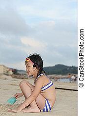 Asian kid on beach - Asian kid in a bikini playing with sand...