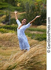 Summer Day - A beautiful Hawaiian woman stands in a meadow...