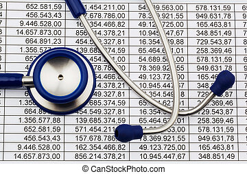 Balance sheet figures and stethoscope - A stethoscope is on...