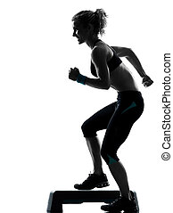 woman exercising step aerobics - one woman exercising...