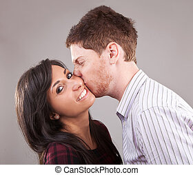 man kissing a young woman