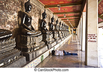Wat Suthat - long row of buddha statues surrounding the...