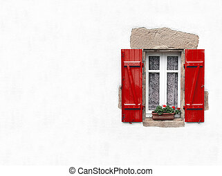 Red shuttered window on white stucco wall with geraniums in...