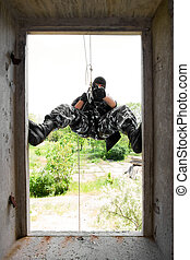 Soldier in black mask entering through the window - Armed...