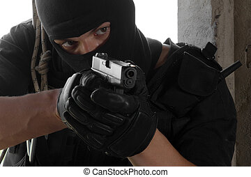 Soldier in black mask targeting with a gun - Armed man in...
