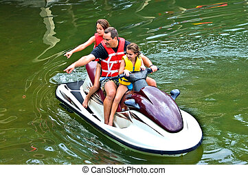 Man and Daughters on Jet Ski Pointing - A man and his...