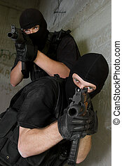 Soldiers in black masks targeting with AK-47 rifles - Photo...