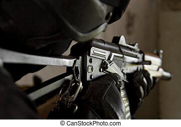 Soldier in bulletproof helmet targeting with AK-47 rifle -...