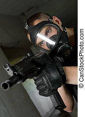 Soldier in gas mask targeting with rifle - Photo of armed...