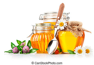 sweet honey in glass jars with spoon and flowers isolated on...