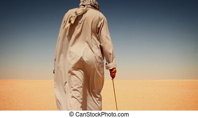 Walk in the desert - Man dressed in a dishdasha passes...