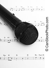 Music - A microphone and sheet music together. The sheet is...