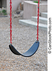 Empty Swing - A single empty child swing with red chains and...