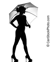 silhouette woman holding open umbrella - full length...
