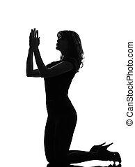 silhouette woman kneel praying imploring - full length...
