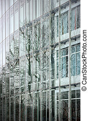 Office building facade, with trees reflected in the glass.
