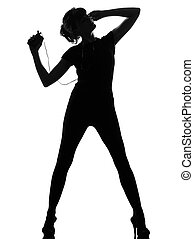 silhouette woman dancing and listening music - full length...