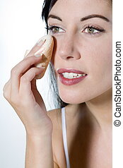 beautiful young woman on studio white isolated background applying face powder make-up