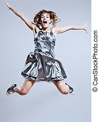 beautiful young girl with prom dress jumping screaming happy...