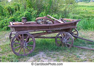 wooden cart - Ancient wooden cart standing on a green grass....