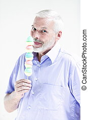 Senior man portrait eating candy - caucasian senior man...