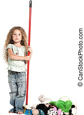 Little girl sweeping toys serious