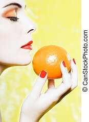 Woman portrait smelling an orange tangerine fruit -...