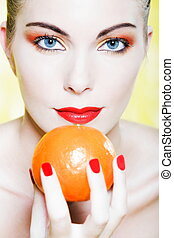 Woman portrait holding a mandarine - beautiful caucasian...