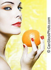 Woman portrait showing a orange tangerine fruit - beautiful...