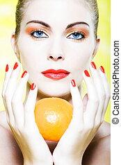 Woman portrait holding a orange tangerine citrus fruit -...