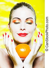 Woman Portrait smelling a citrus fruit smiling