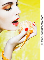 Woman Portrait eating a mandarin orange tangerine fruit -...