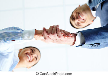 Deal - Below angle of successful associates handshaking...