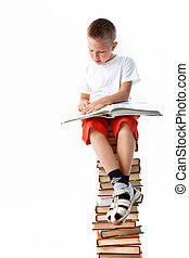 Reading - Image of schoolboy sitting on the heap of books...