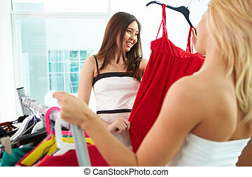 Selecting clothes - Image of pretty females looking at smart...