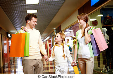 Family of shoppers - Image of family carrying bags and...