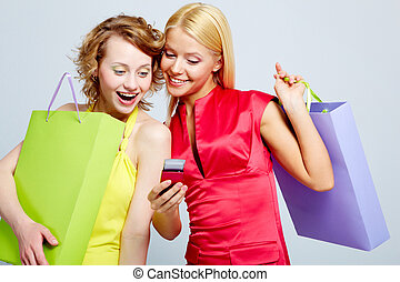 Female shoppers - Gorgeous shoppers reading sms on mobile...