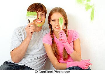 Artists - Image of joyful guy and girl hiding one of eyes...