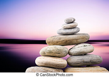 Pebbles stack in peaceful evening with smooth ocean...