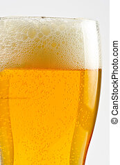 Glass of beer closeup on a white background