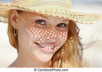woman in straw hat smiling at camera