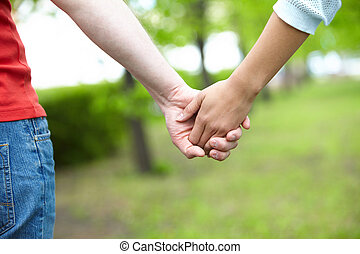 Togetherness - Close-up of female and male holding by hands...